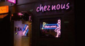 """Eingangstür und Schaufenster des Nachclubs """"Nacht Clubs"""" in Köln, erleuchtet von pinken Neonlichtern, einer pinken Frauensilhouette, dem Namen in Leuchbuchstaben und einem gelben Champagnerglas"""