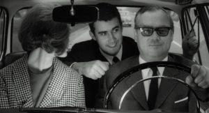 Drei Personen in einem schwarz-weiß Bild aus den 1960ern. Am Steuer Leo Wagner, neben ihm eine Frau und auf der Rückbank ein Mann, der eine Faust macht.